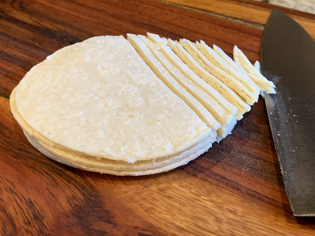 """Small round soft corn tortillas partially sliced to 1/8"""" thick strips laying on a wood cutting bored with a chef knife."""