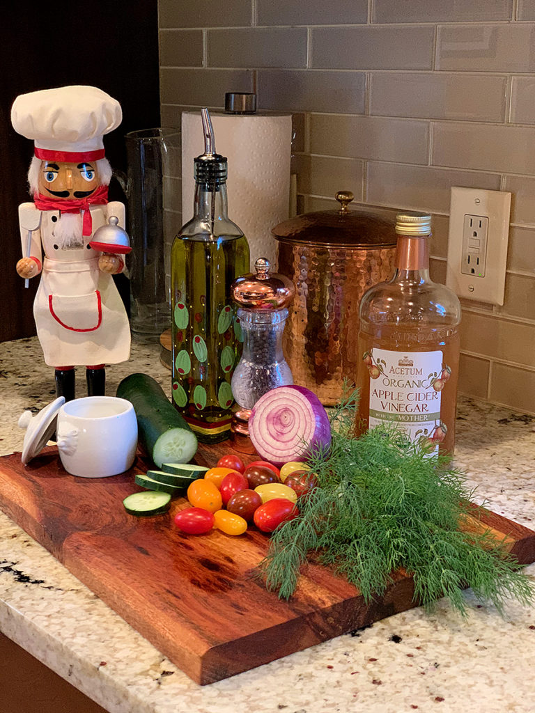 Ingredients to make tomato, cucumber, dill and red onion salad including olive oil, apple cider vinegar, salt & pepper. All on a nice wood board with a nutcracker who looks like a chef.