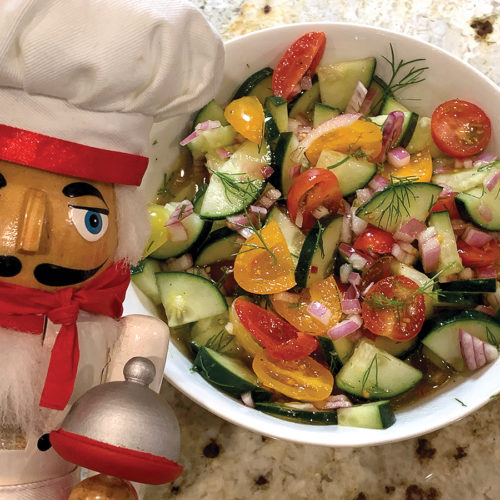 Chopped tomato, cucumber, red onion and dill salad in a round white bowl with a nutcracker in the foreground who looks like a chef.