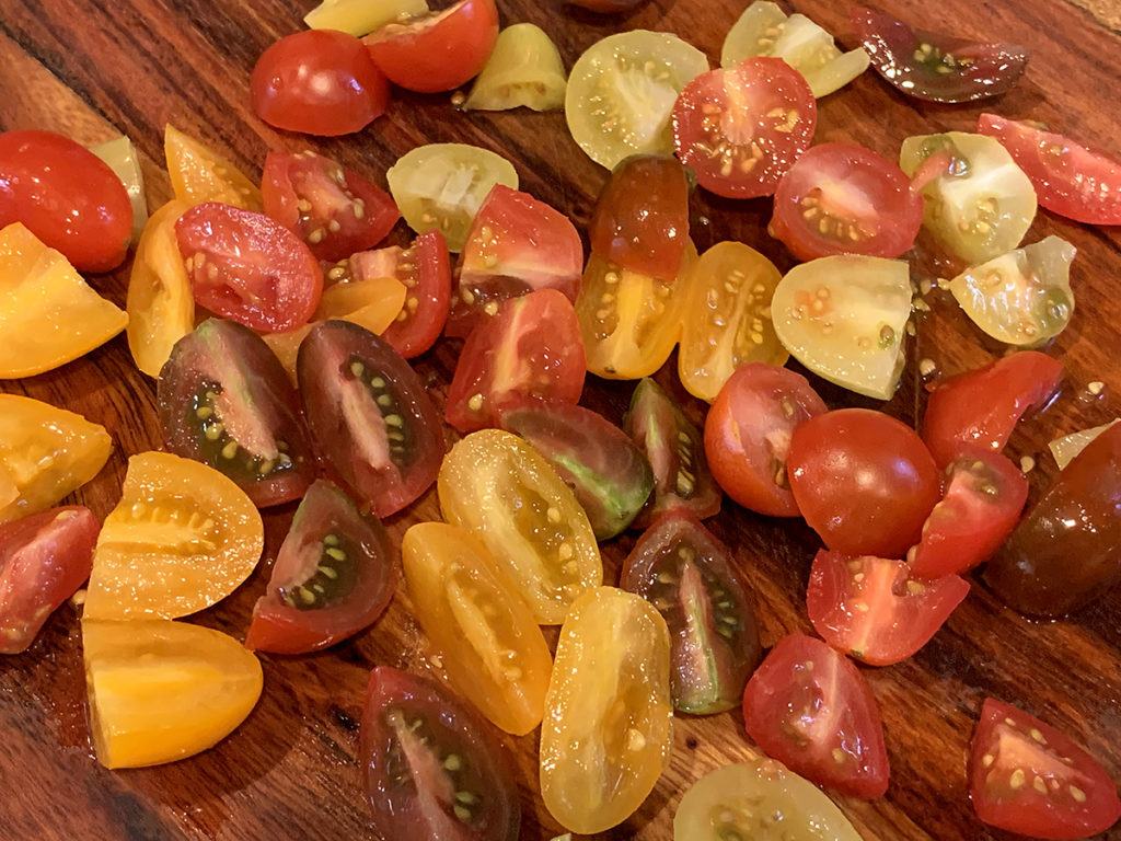 colorful blend of cherry tomatoes, quartered on a nice wood cutting board.