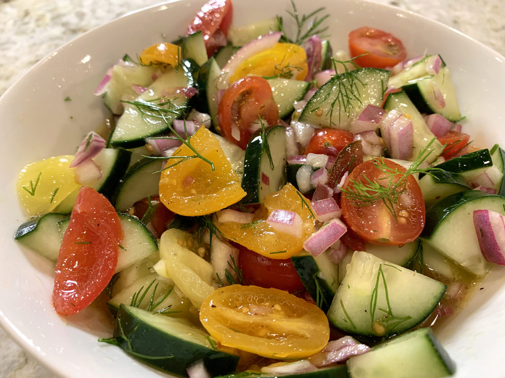 Chopped tomato, cucumber, red onion and dill salad in a round white bowl.