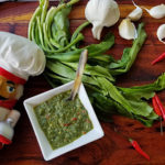 Culantro leaves, garlic cloves, whole red Thai chilies and a small white dish with a green sauce, all sitting on a pretty wood board. There's a nutcracker in the foreground who looks like a chef.