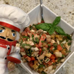 Chicken Panzanella Salad in a square white bowl with a fresh basil garnish and a nutcracker in the foreground who looks like a chef.