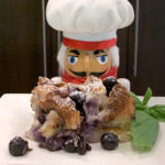Blueberry bread pudding on a white plate with fresh basil garnish and a nutcracker who looks like a chef in the background