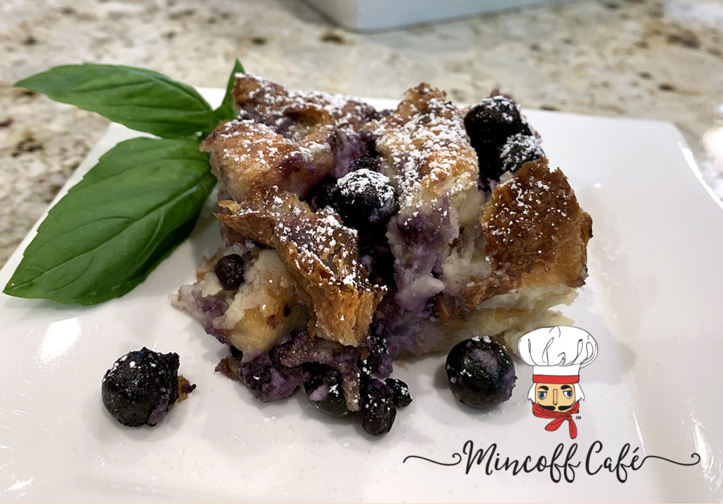 Blueberry & Cream Cheese Croissant Puff on a white plate with fresh basil garnish.