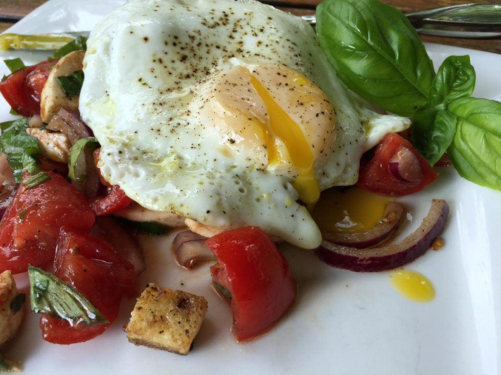 Panzanella salad topped with a fried egg that is cut so the yolk runs out.