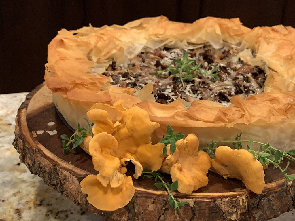 Rustic chanterelle tart with ruffled filo dough crust sitting on a round wood pedestal that has bark around the edge. There are a few raw, whole chanterelles and some fresh thyme on the board for garnish.