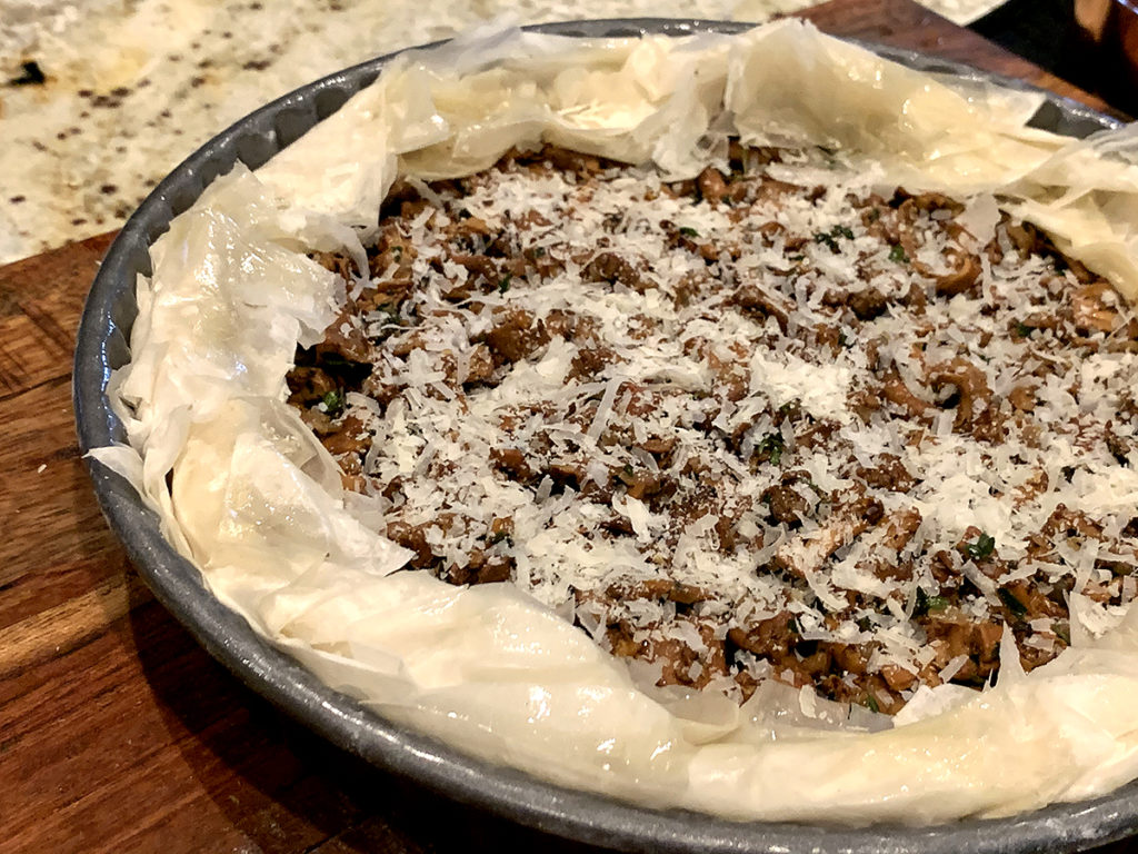 Chanterelle duxelles in a round tart pan with ruffled filo dough around the edges and cheese sprinkled on the top, ready for the oven.