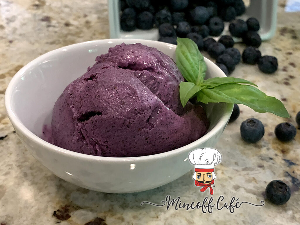 Scoops of blueberry ice cream in a small, white, round bowl and garnished with basil. Fresh blueberries in the background.
