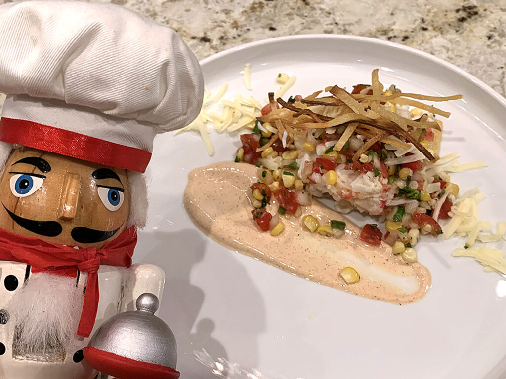 king crab, pico de gallo and chipotle cream sauce on a round white plate. There's a nutcracker in the foreground that looks like a chef.