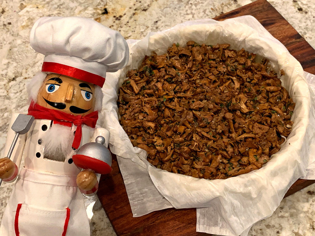 Chanterelle duxelles on multiple layers of phyllo dough in a tart pan. There's a nutcracker who looks like a chef in the foreground.