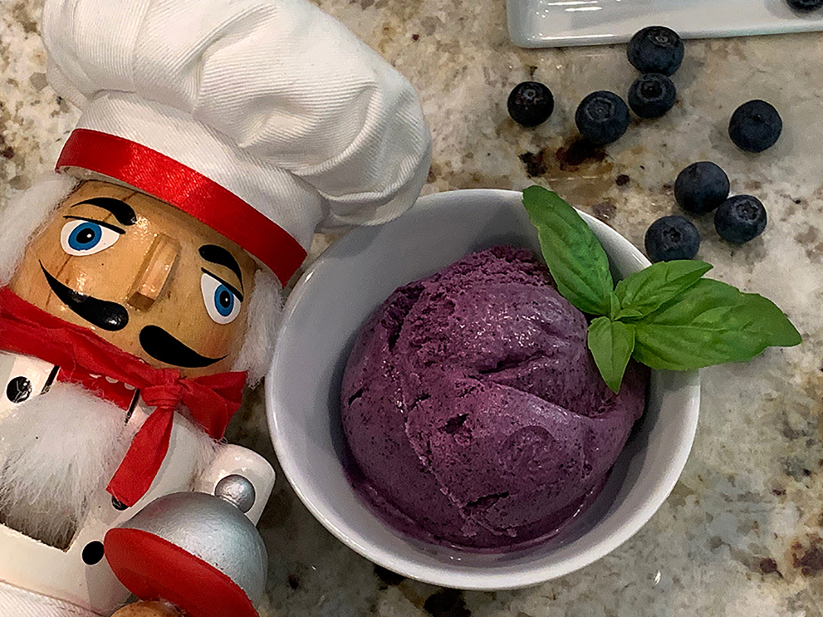 Scoops of blueberry ice cream in a small, white, round bowl and garnished with basil. Fresh blueberries in the background. There's a nutcracker who looks like a chef in the foreground.