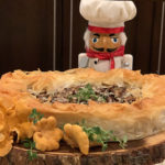 Rustic chanterelle tart with ruffled filo dough crust sitting on a round wood pedestal that has bark around the edge. There are a few raw, whole chanterelles and some fresh thyme on the board for garnish and a nutcracker who looks like a chef in the background.