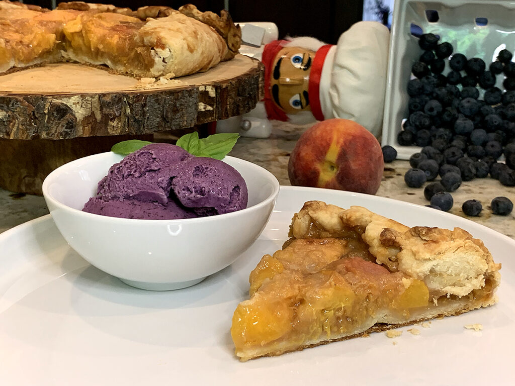 A small white bowl with Blueberry ice cream garnished with fresh basil, a slice of peach galette on a white plate. There's a nutcracker, fresh peaches and blueberries in the background.
