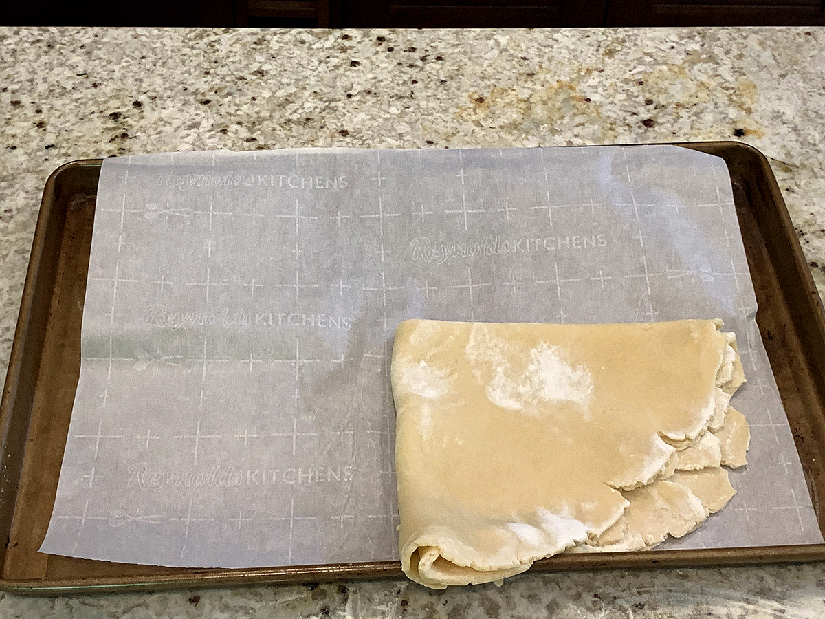 Rolled out pastry dough that has been folded into fourths and is sitting on the bottom right corner of a parchment lined sheet pan.