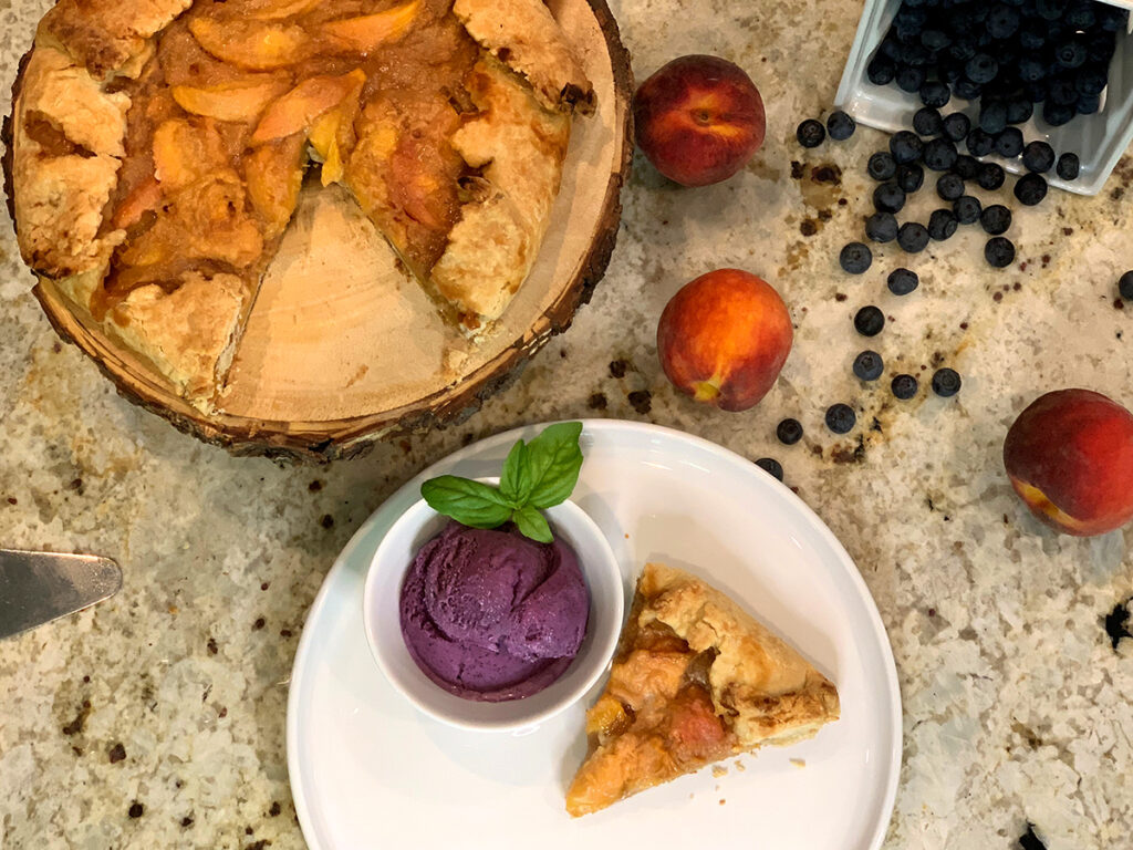 Overhead view of one piece of peach galette and a small bowl of blueberry ice cream all on a round white plate. There's the rest of the galette, fresh peaches and fresh blueberries above.