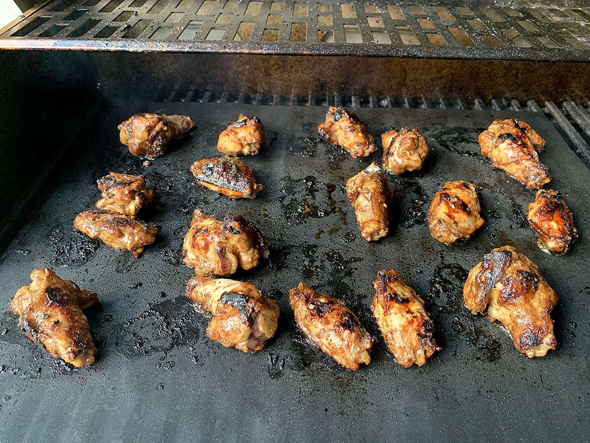 17 Wings cooking on a grill mat on a propane grill.