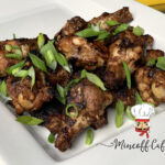 Grilled chicken wings on a square white plate, garnished with chopped green onions.