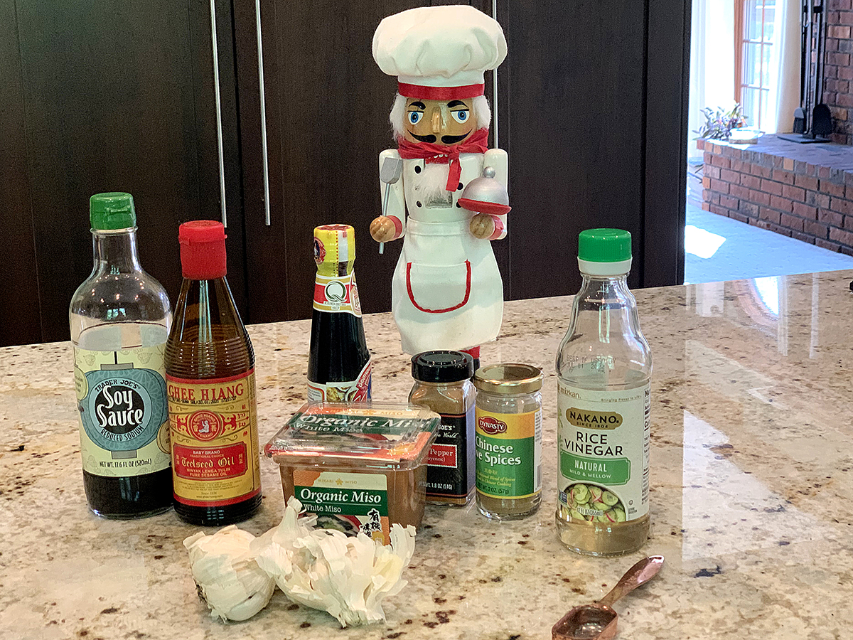 Several bottles of ingredient, a couple of heads of garlic, a tub of miso paste, and a nutcracker who looks like a chef.