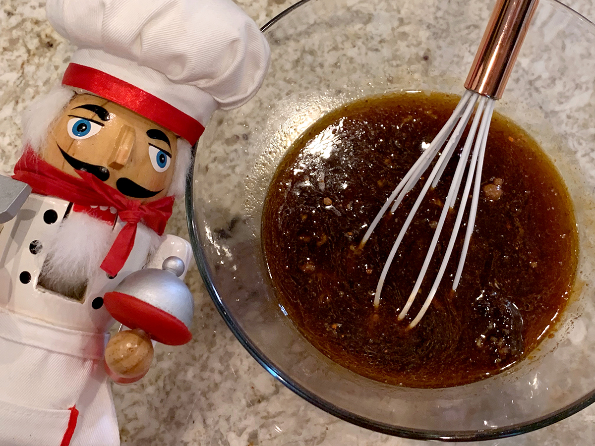 Brown sauce in a clear bowl with a whisk. There's a nutcracker who looks like a chef in the foreground.