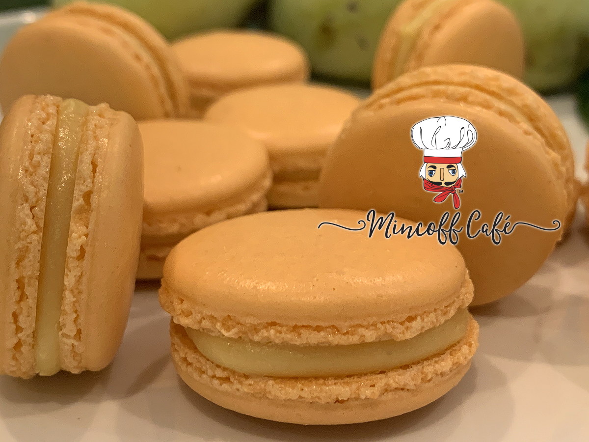 Close up view of pale orange pawpaw french macarons.