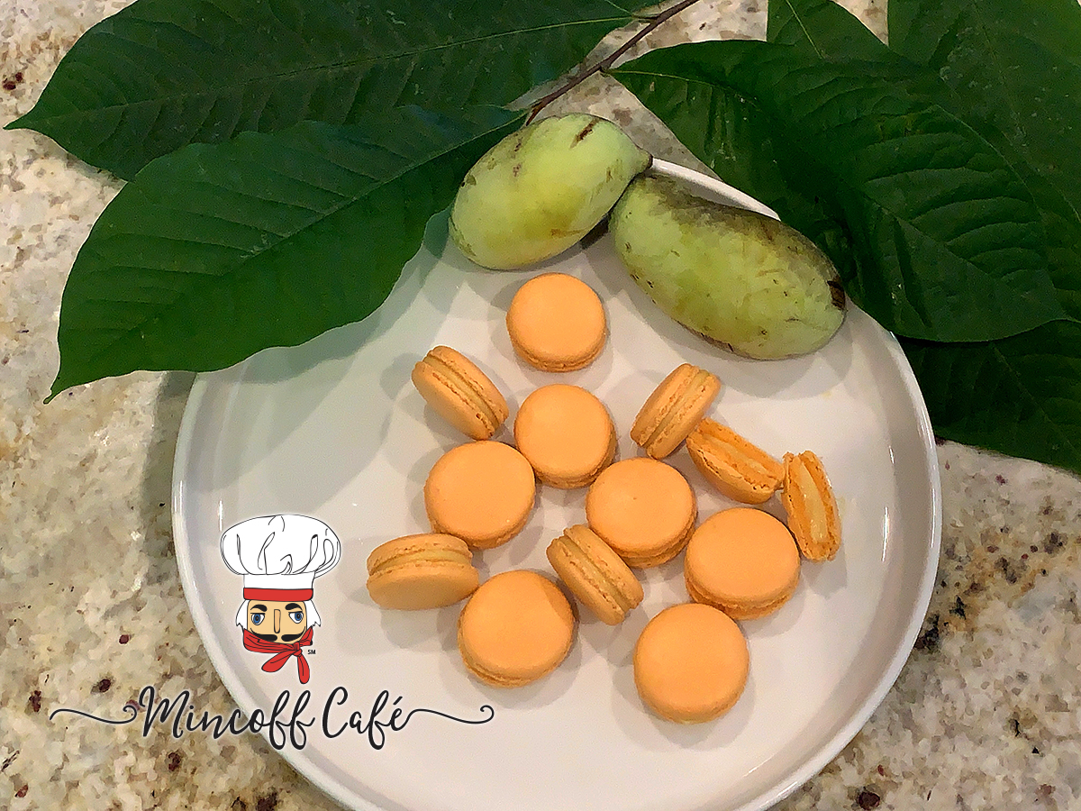 pale orange pawpaw french macarons on a round white plate with fresh pawpaw fruit and pawpaw leaves.