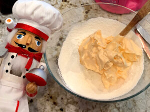 Pale orange meringue being mixed with almond flour and sugar in a clear bowl. There's a nutcracker who looks like a chef in the foreground.