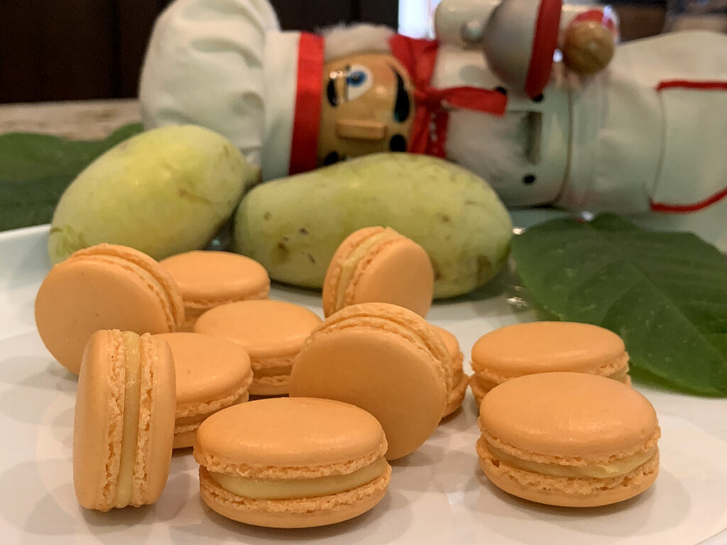 Pale orange macaron cookies on a white plate with fresh green pawpaw and a nutcracker who looks like a chef in the background.