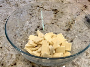 Chunks of white chocolate in a clear glass bowl.
