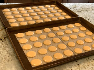 Two sheet pans with 20 round, orange disks of macaron batter.