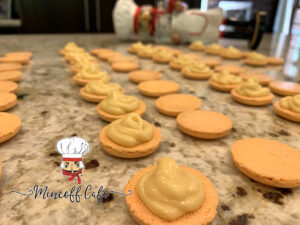 Pale orange round macaron shells face up, in rows on a granite counter top. Every other one has a pale yellow orange dollop of pawpaw white chocolate ganache on it. There's a blurry image of a nutcracker who looks like a chef in the background.