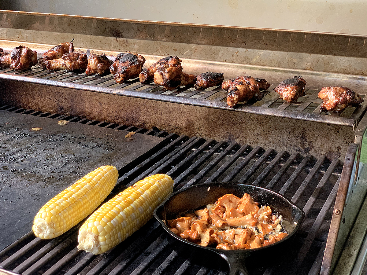 Chicken wings, corn on the cob and chanterelles in a skillet all on the propane grill.