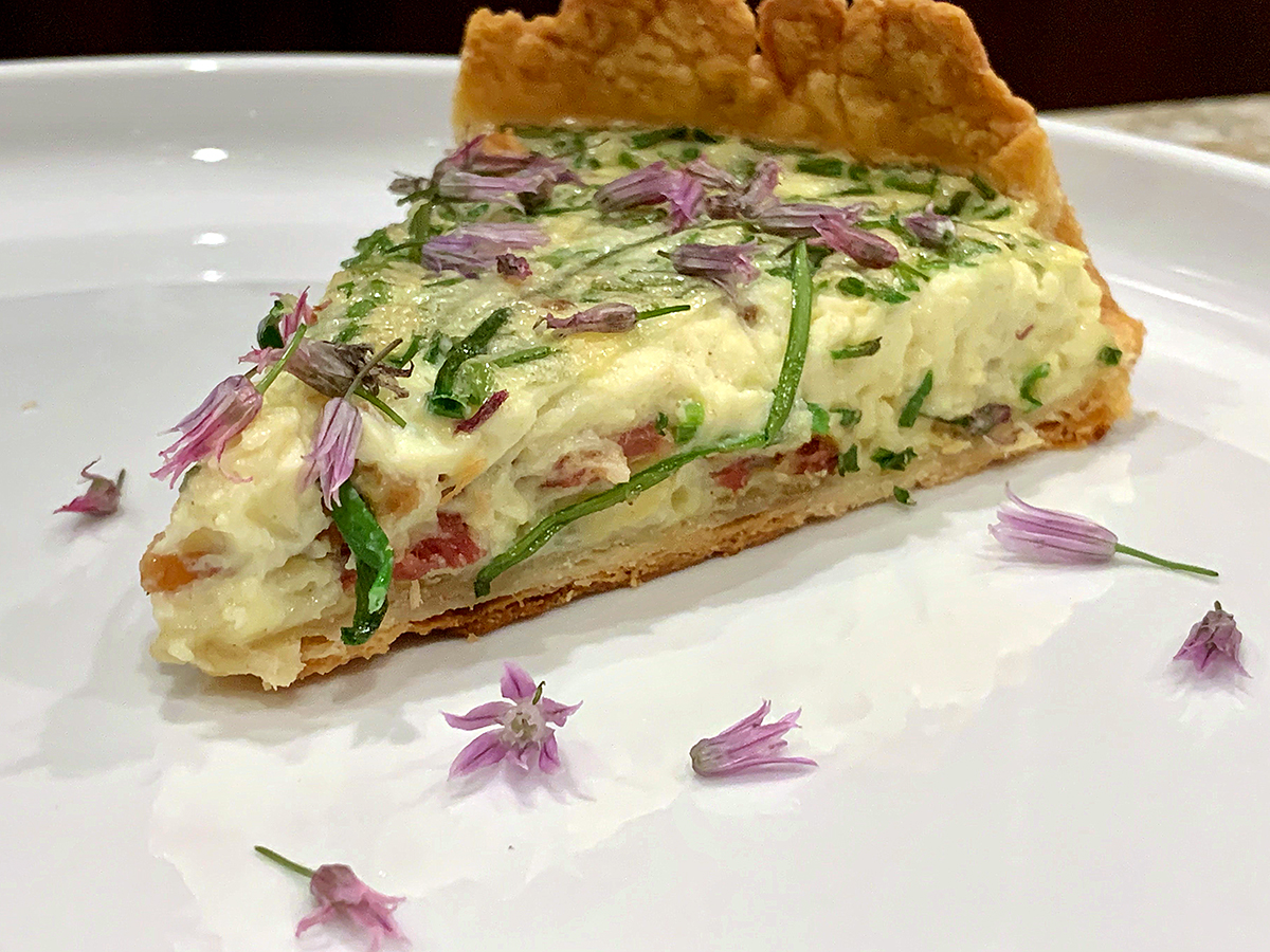 A wedge of bacon, chive and gruyere quiche garnished with chive petals on a round white plate.