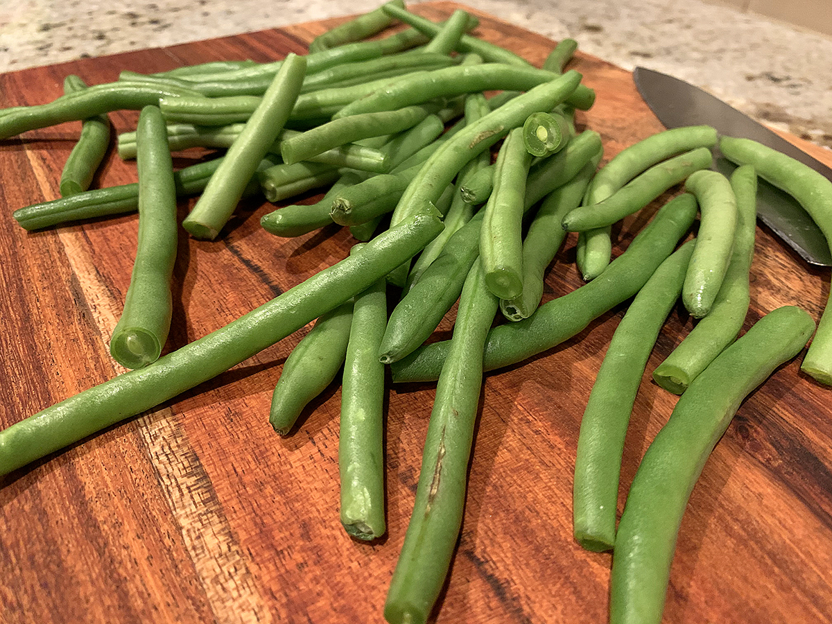 Fresh green beans on a wood cutting board.