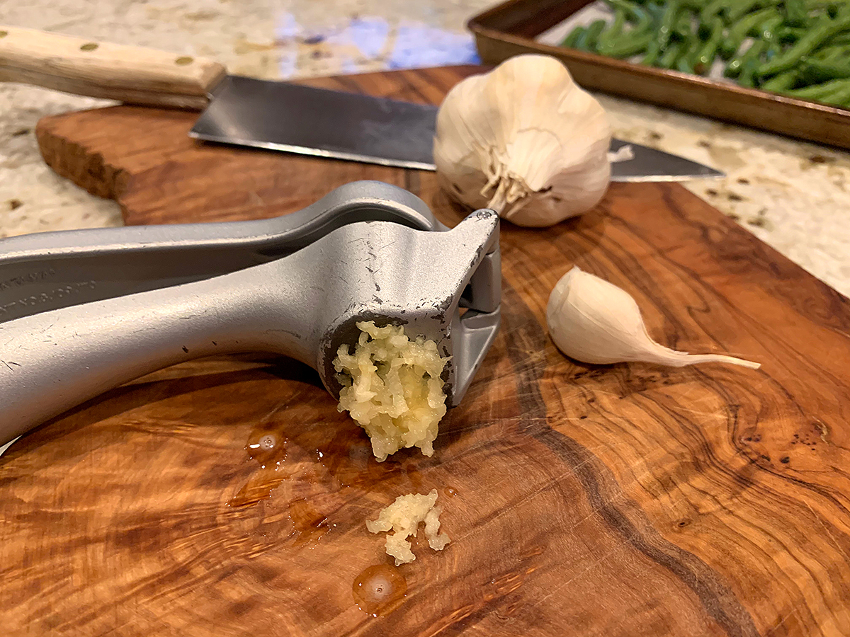 Silver garlic press with garlic being pressed out of the holes. It's laying on a wood board and there's whole garlic in the background.
