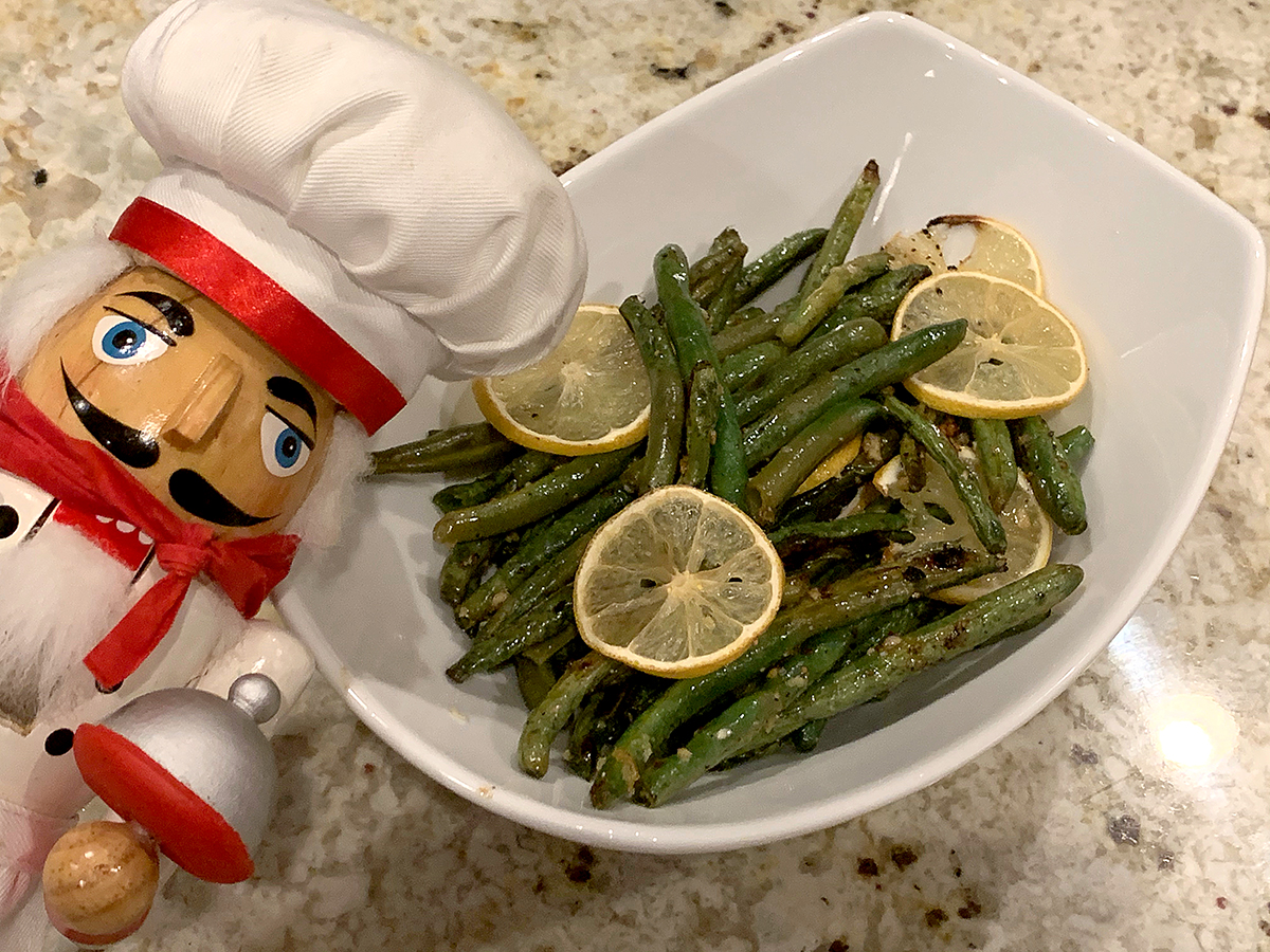 Roasted green beans with slices on lemon on top in a white bowl. There's a nutcracker who looks like a chef in the foreground.