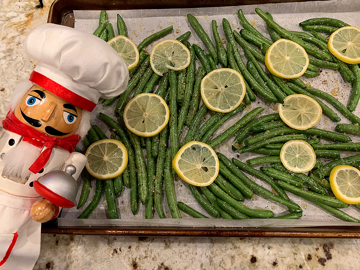 Single layer of roasted green beans with sliced lemons on top. There a nutcracker who looks like a chef in the foreground.