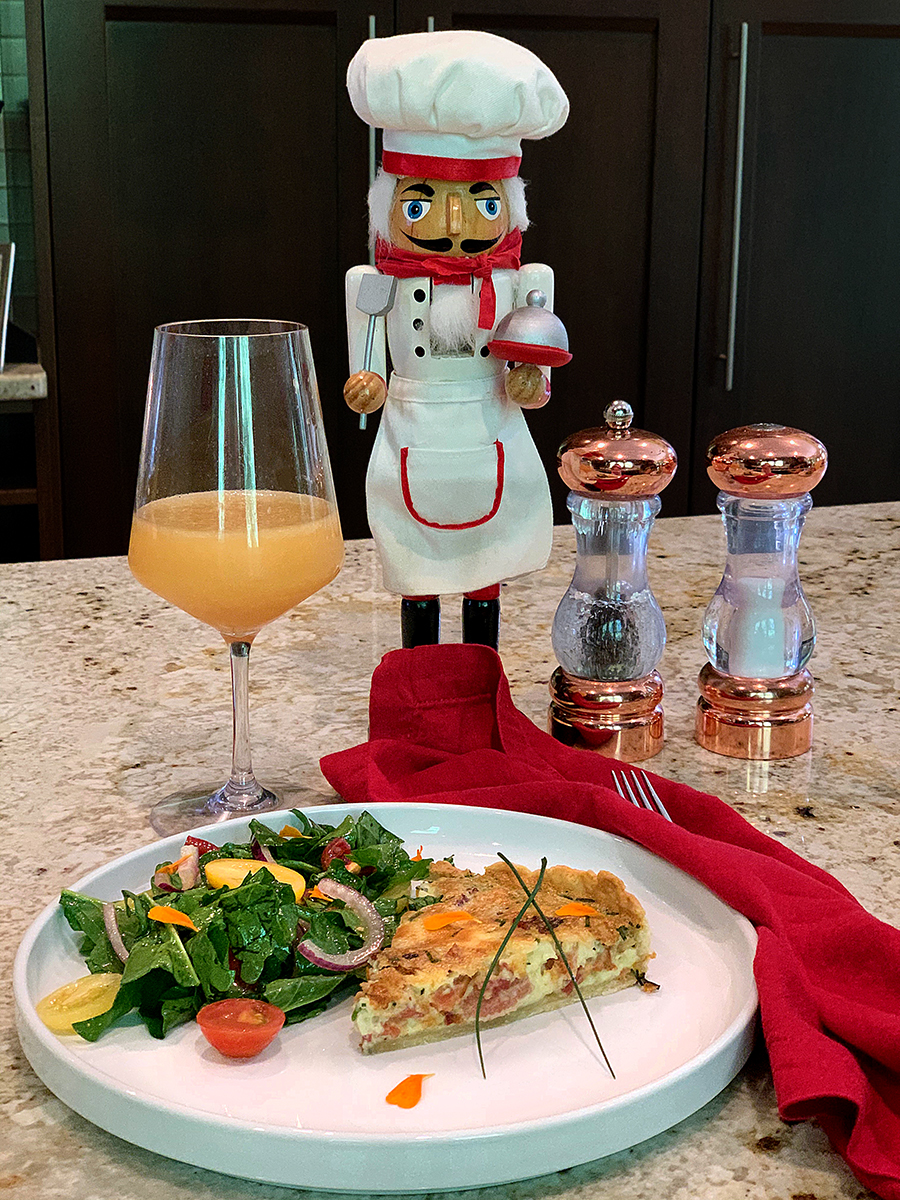 A wedge of bacon, chive and gruyere quiche wish a side salad, garnished with flower petals on a round white plate. There a mimosa, a nutcracker who looks like a chef and salt & pepper shakers in the background.