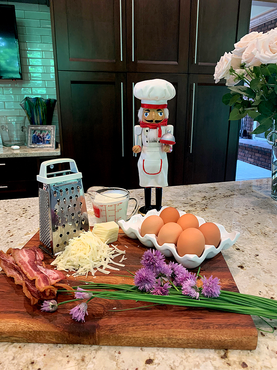 Bacon, eggs, chives, chive blossoms, milk grated gruyere cheese and a box grater, all on wood cutting board with a nutcracker who looks like a chef in the background.