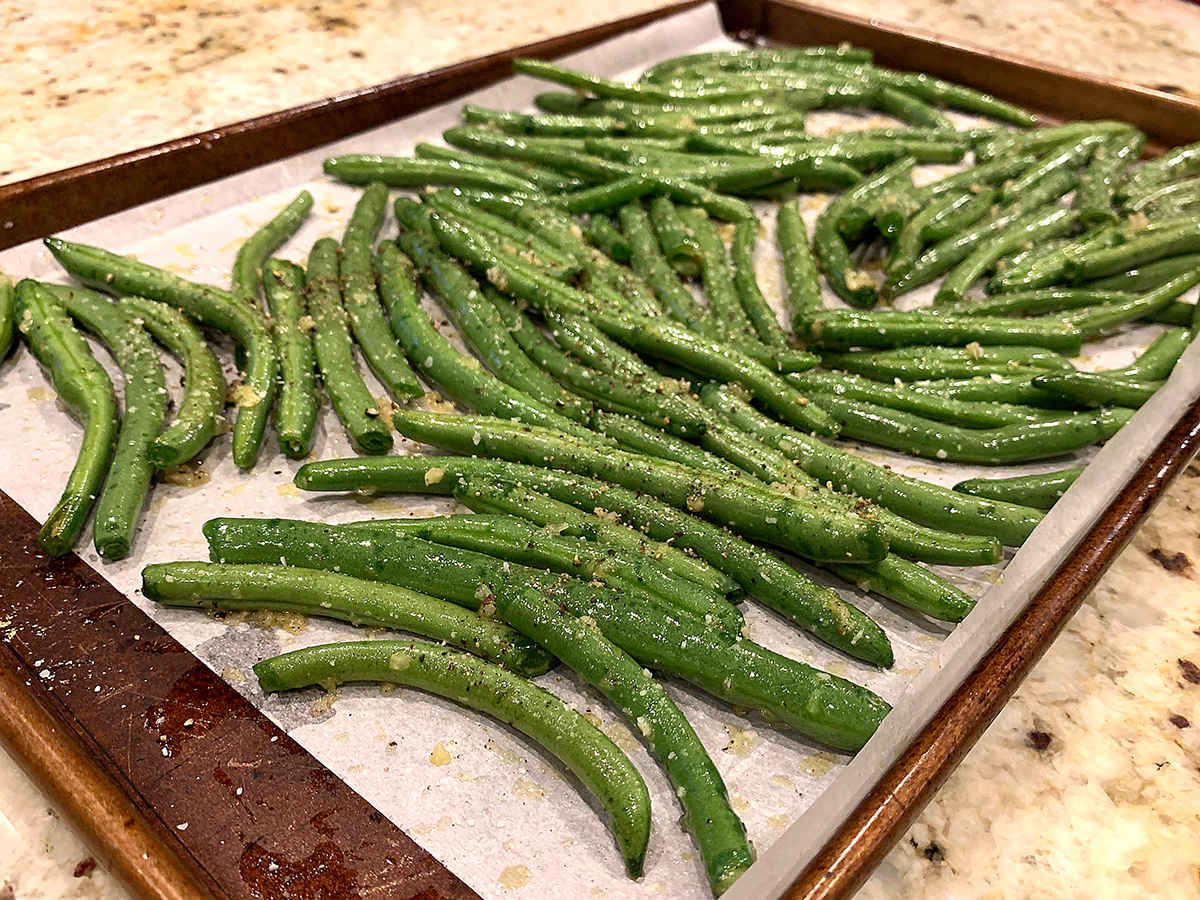 Single layer of fresh green beans on a sheet pan lined with parchment paper.