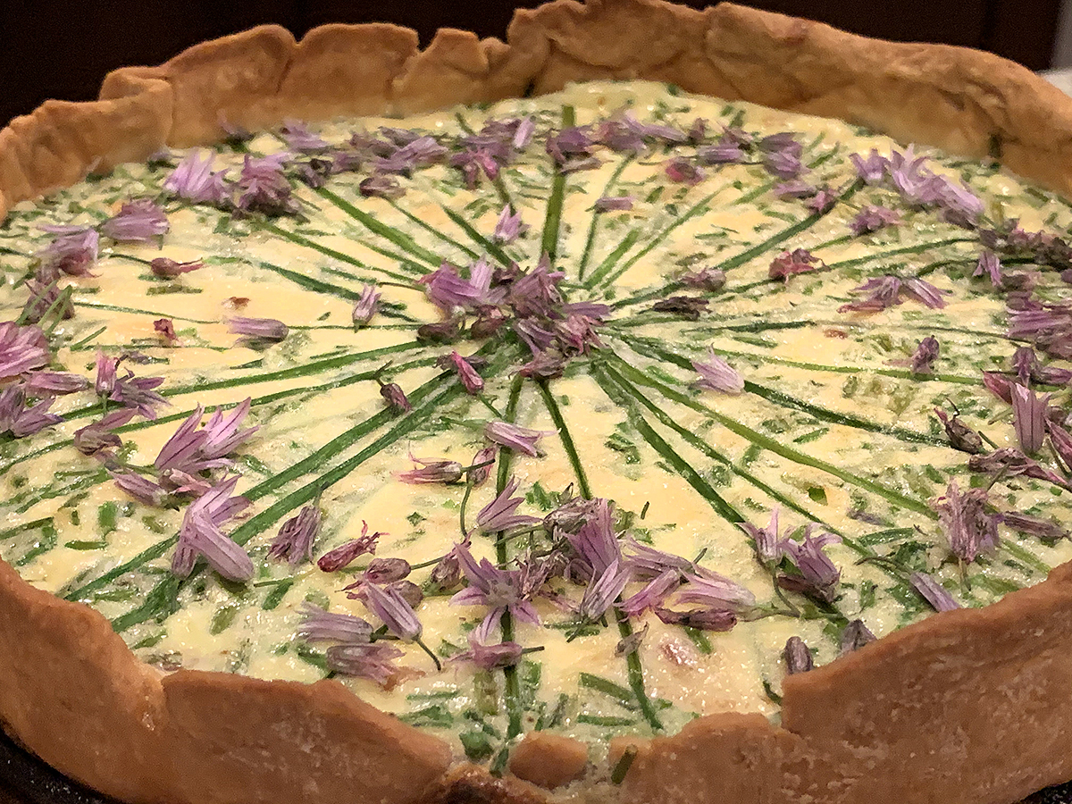 Beautiful quiche garnished with fresh chives and chive blossom petals.