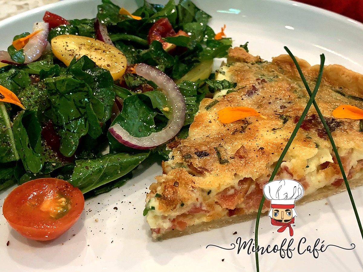 A wedge of bacon, chive and gruyere quiche wish a side salad, garnished with flower petals on a round white plate.