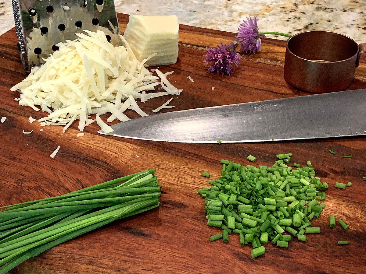 Chopped chives and shredded gruyere cheese on a wood cutting board.
