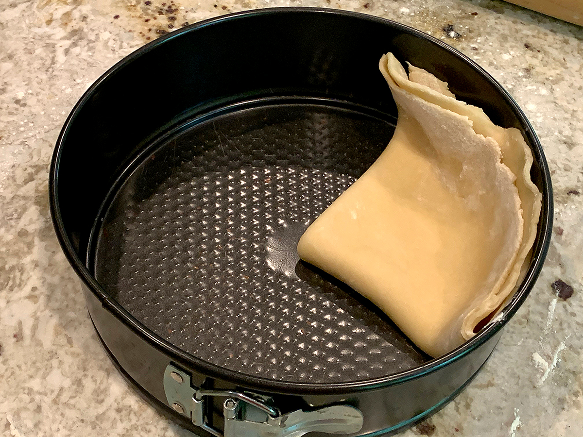 Pastry dough folded in quarters and laying in a spring form pan. The corner is is the center and the edge runs up the side of the pan. It's ready to unfold.