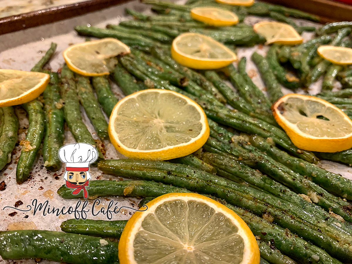 Single layer of roasted green beans with sliced lemons on top.
