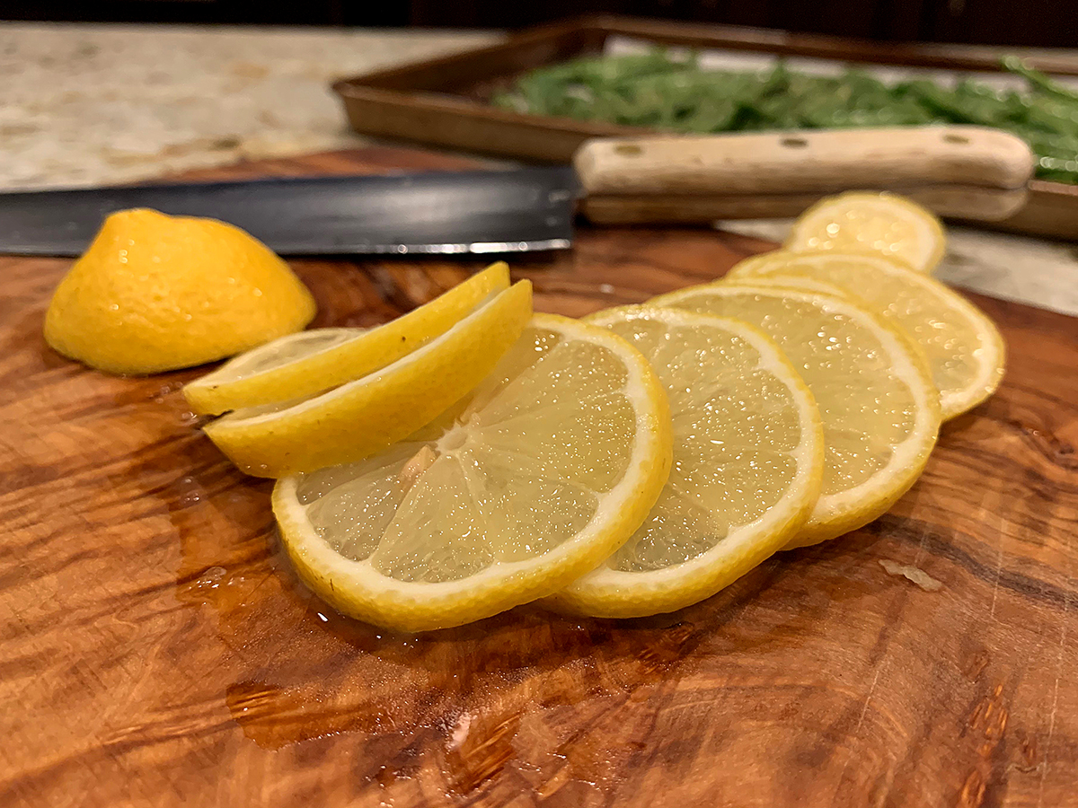 Several lemon slices on a wood cutting board.