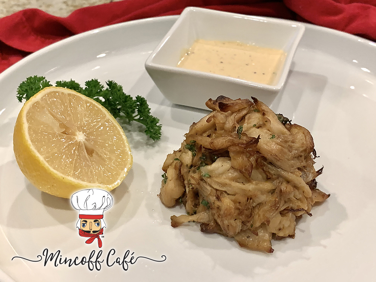 Crab cake mound on a round white plate with a square ramekin of pale yellow sauce, a lemon wedge and some parsley.