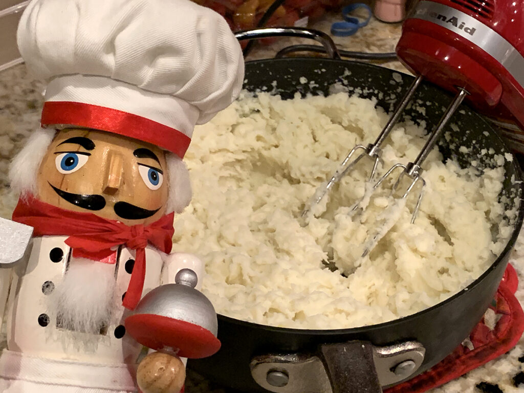 Whipping mashed potatoes with a hand mixer in a grey saucepan. There's a nutcracker who looks like a chef in the foreground.