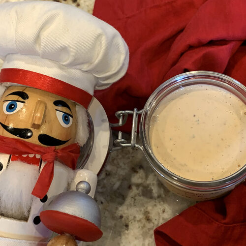 Pale orange sauce in a glass jar with a hinged lid. There's also a nutcracker who looks like a chef in the foreground.