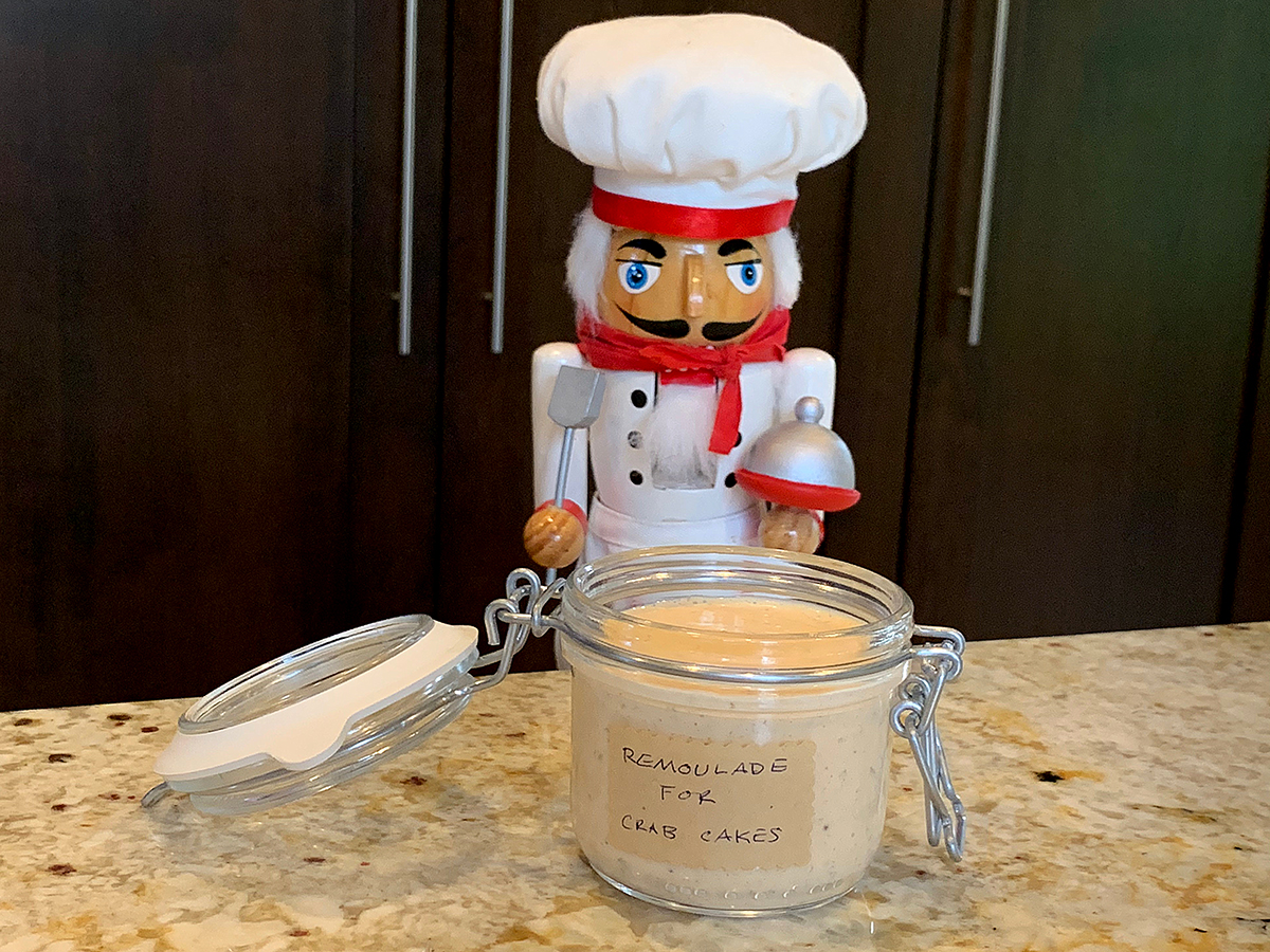 Pale orange sauce in a glass jar with a hinged lid. There also a nutcracker who looks like a chef in the background.